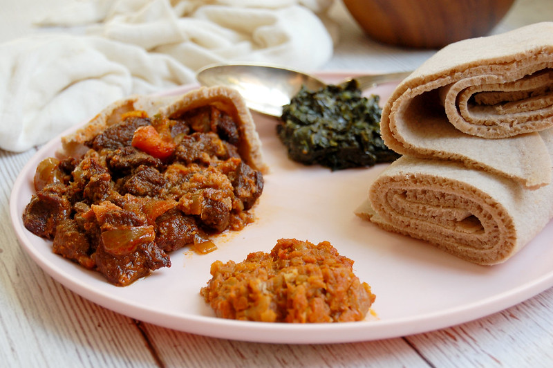 platter of ethiopian beef tibs with injera spinach and lentils