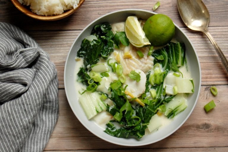 finished bowls of coconut milk poached fish in bowl with bok choy and lime
