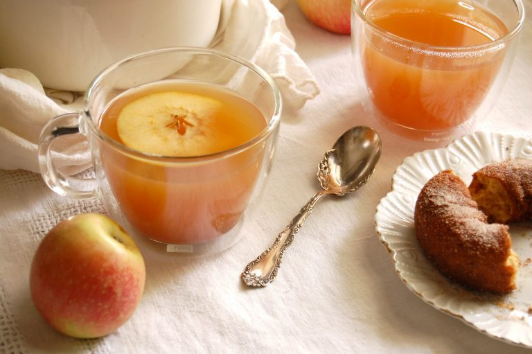 glass mugs of mulled apple cider with pot