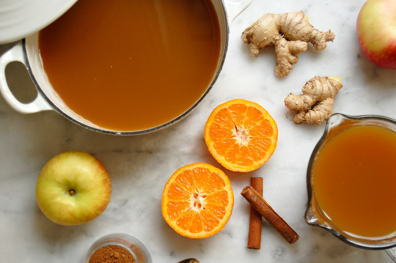 pot of apple cider with mulling ingredients oranges cinnamon sticks ginger gloves