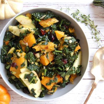 kale and roasted butternut squash salad with apple cider vinaigrette on table with pumpkins fall salad
