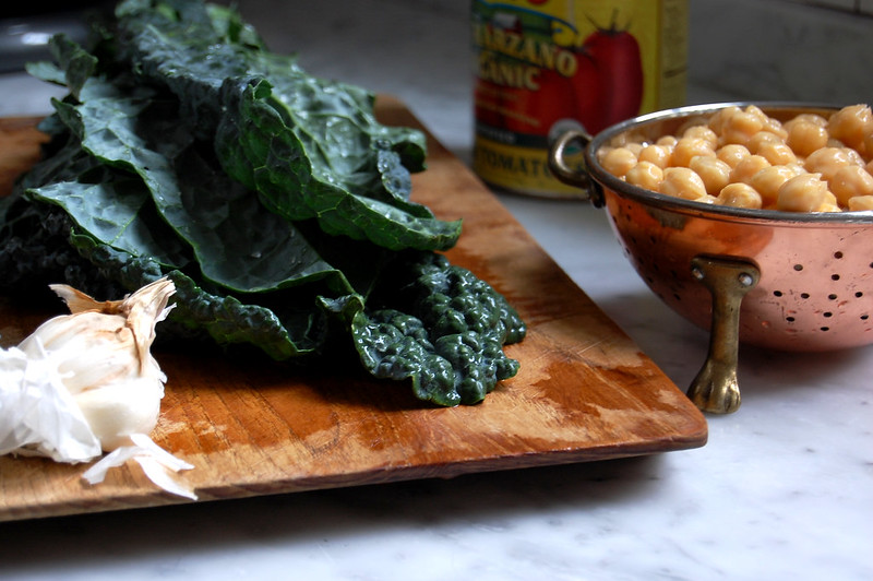 kale on cutting board with chickpeas and tomatoes