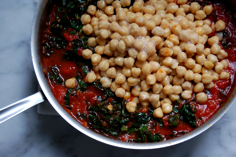 skillet with tomatoes kale and chickpeas for stew
