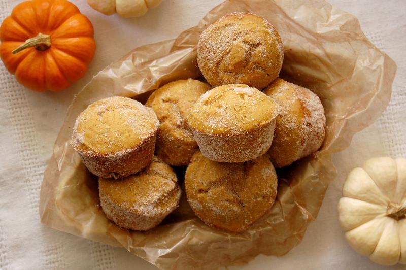 basket of baked pumpkin dounts rolled in cinnamon sugar with mini pumpkins