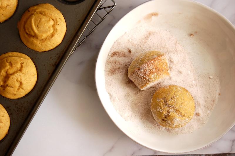 pumpkin donut muffins getting rolled in cinnamon sugar after baking