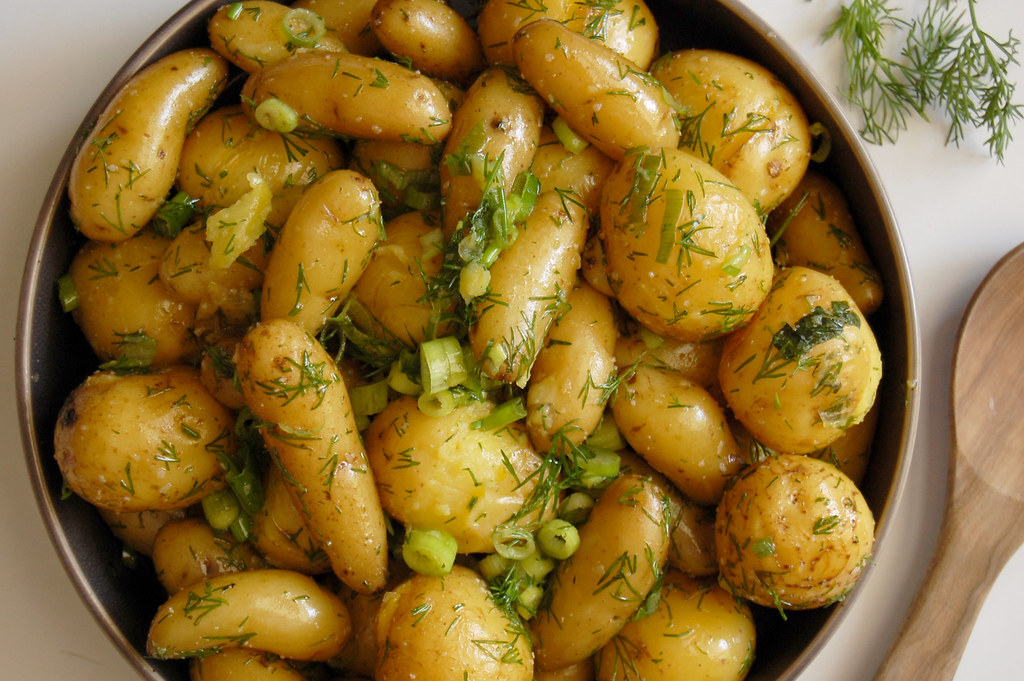 bowl of cooked dilly scallion potatoes in bowl with wooden spoon