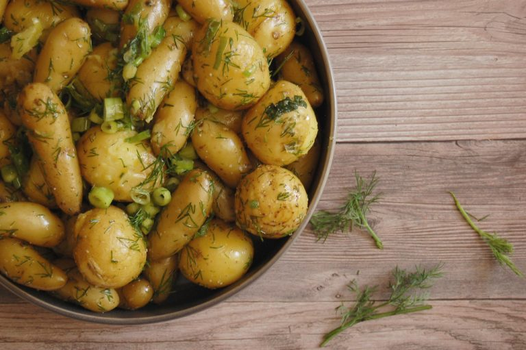platter of cooked potatoes with scallions and dill on wooden table