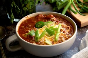 bowl of beans vegetarian chili with cheese and scallions on top