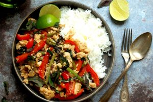 dish of chicken kra pao with peppers and basil served with lime and rice