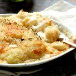 baked creamy cauliflower gratin in casserole with spoon