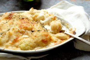 baked creamy cauliflower gratin in casserole with spoon