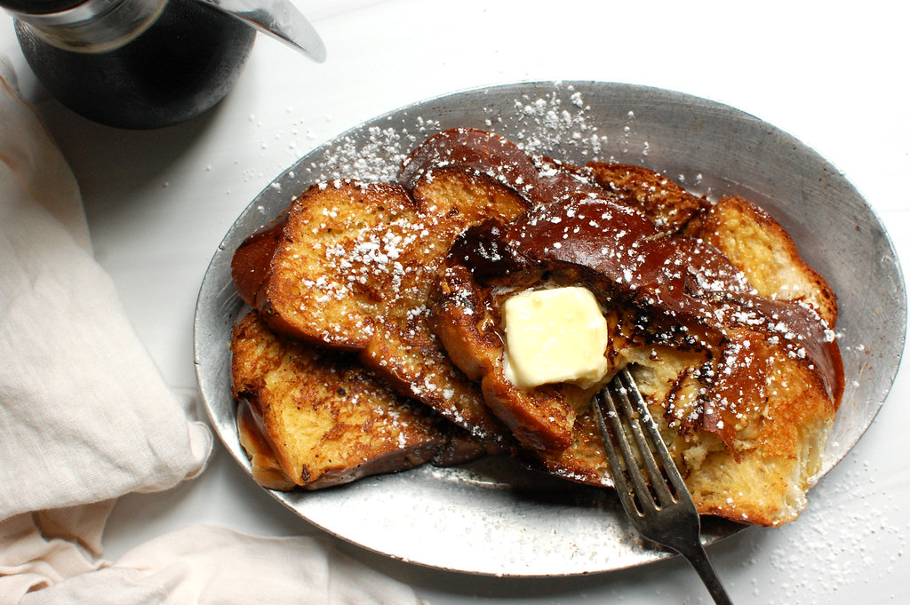 A platter of skillet French toast with maple syrup and butter