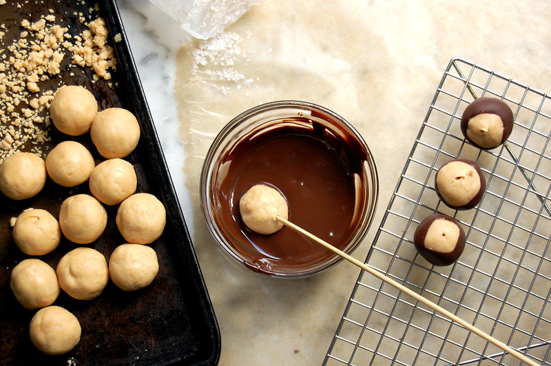 peanut butter balls being dipped in chocolate for buckeyes
