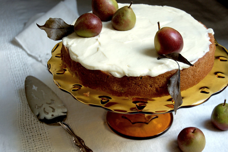 pear cake on cake pedestal with fresh pears on top