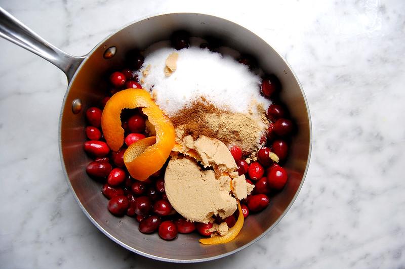 homemade Thanksgiving cranberry sauce ingredients in pot brown sugar, orange, ginger, brown sugar, cinnamon