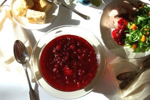 bowl of homemade cranberry sauce with plate of Thanksgiving turkey and salad