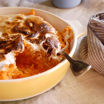 casserole of candied brown sugar sweet potatoes with toasted marshmallow on top with spoon with other Thanksgiving sides