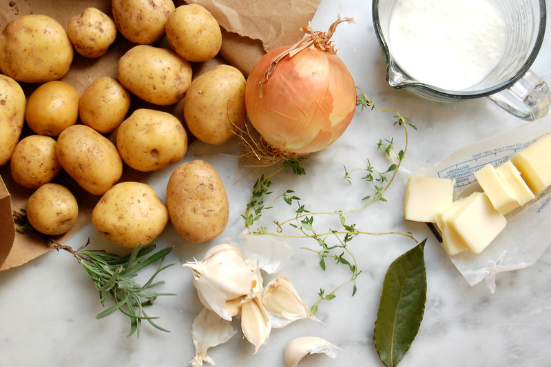 mashed potato ingredients on marble potatoes onion garlic bay thyme