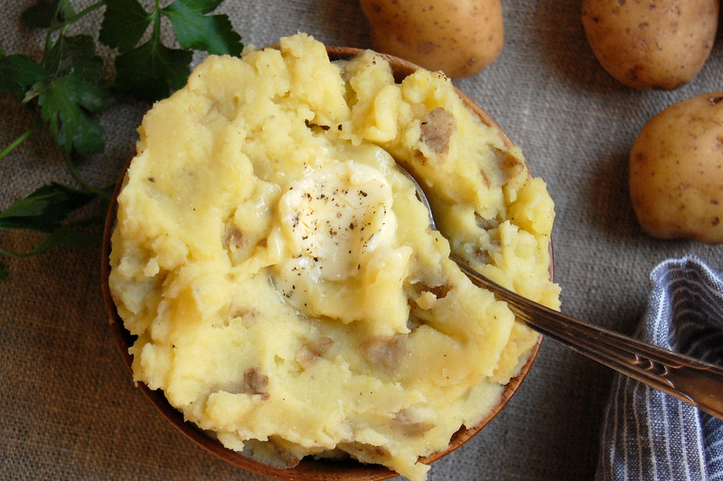 bowl of mashed potatoes with onion garlic thyme and butter