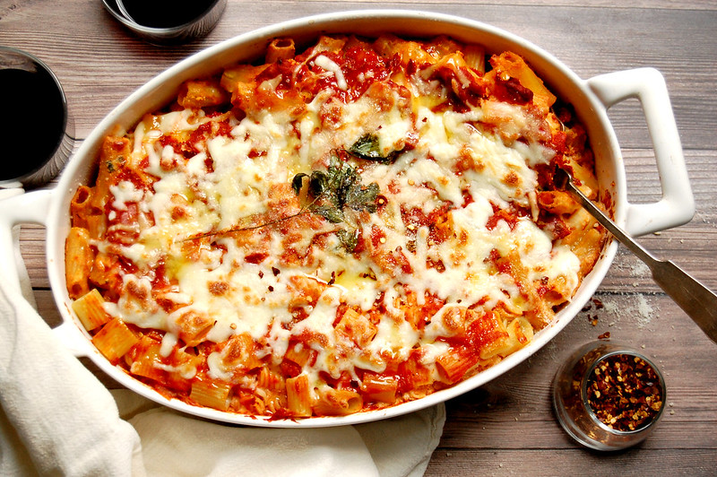 Italian baked ziti casserole with tomato sauce on wood with red wine