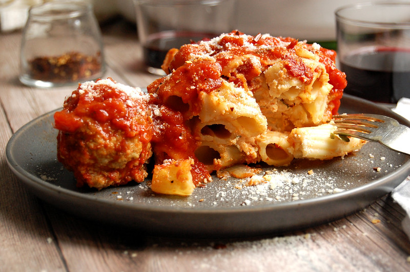 plate of Italian baked ziti with ricotta and meatballs and tomato sauce