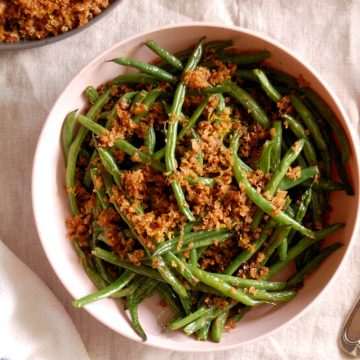 bowl of roasted green beans with buttered breadcrumbs with lemon zest and shallot