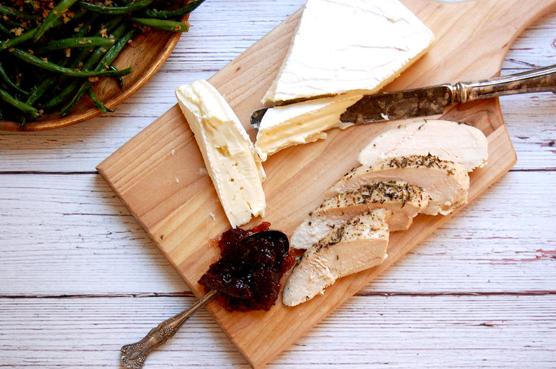 wooden cutting board with sliced turkey brie and a spoonful of cranberry sauce