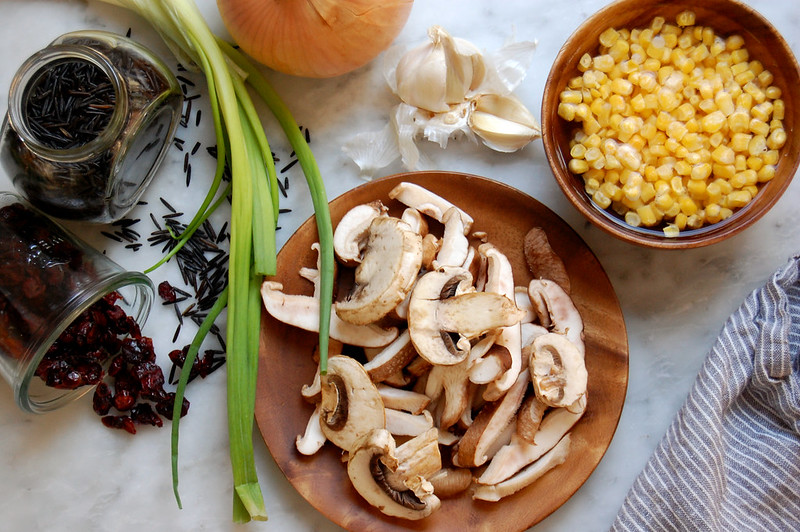 ingredients for wild rice salad mushrooms corn scallions onion garlic on marble