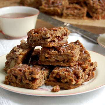 stack of pecan pie toffee bars squares on plate with tea