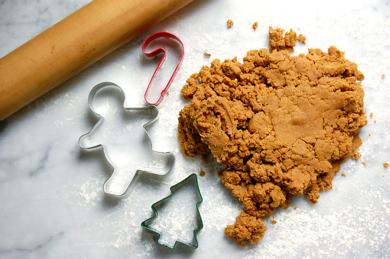 gingerbread cookie dough on marble with cookie cutters and rolling pin