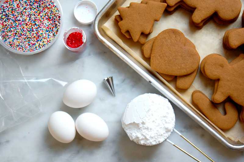 gingerbread cookies on baking sheet about to get decorated with royal icing and sprinkles