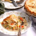 baked deep-dish chicken pot pie with piece on place