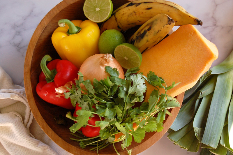 soup ingredients in wooden bowl peppers lime plantains squash onion