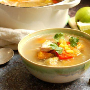 bowl of venezuelan chicken stew with corn cilantro lime in bowl with garnishes