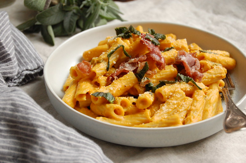 bowl of rigatoni pumpkin pasta sauce with prosciutto and sage for an easy fall and winter dinner