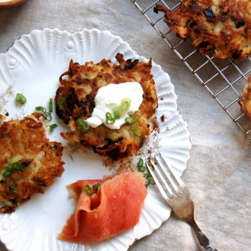 crispy potato latkes on plate with salmon and sour cream