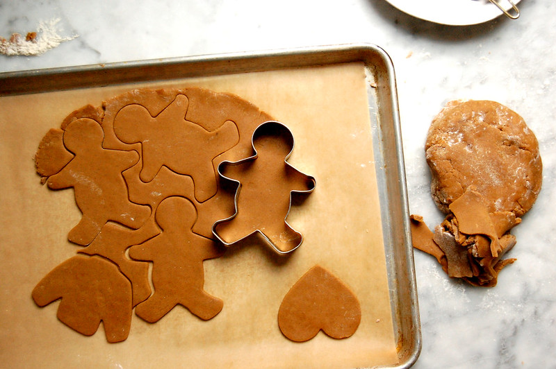 spiced gingerbread cookie dough on sheet pan being cut out with cookie cutters