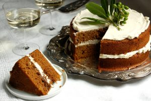 sliced gingerbread layer cake on table with champagne and holly