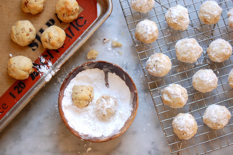 snowball cookies baked cookies getting rolled in powdered sugar