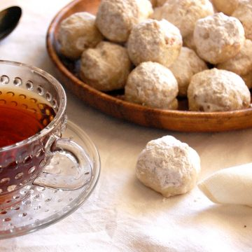 plate of snowball cookies mexican wedding cookies russian tea cakes with cup of tea
