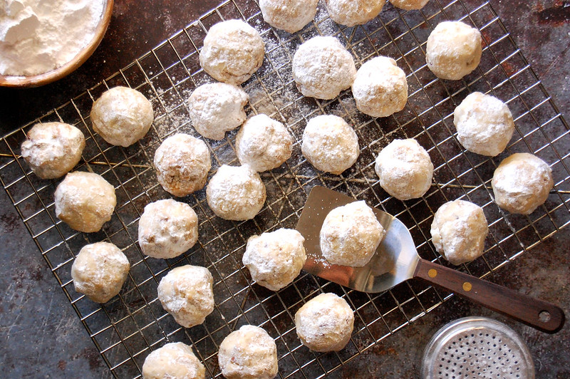 cooling rack of baked snowballs mexican wedding cookies with powdered sugar