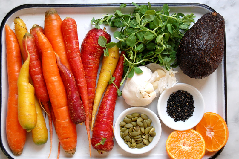 carrots seeds garlic sprouts citrus and avocado on tray for carrot side dish