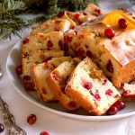 white platter of slice cranberry orange nut bread with holiday christmas greens