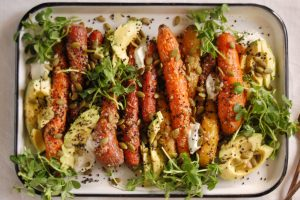platter of roasted carrots with avocado sprouts and seeds from abc kitchen
