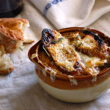 crock of French onion soup with baguette and melted cheese