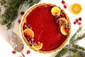 cranberry curd tart decorated with orange and rosemary and fresh cranberries