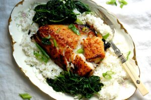 cooked miso-marinated black cod on bed of white rice with greens, ready to be served for fish dinner