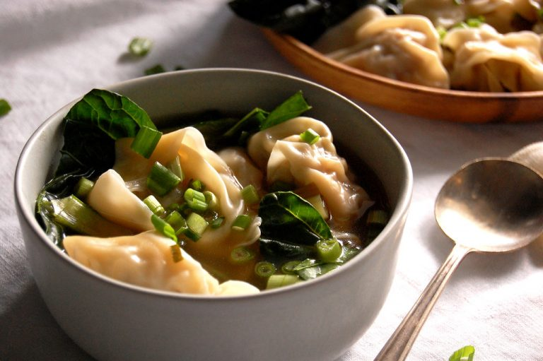 bowl of wonton soup with greens and scallions
