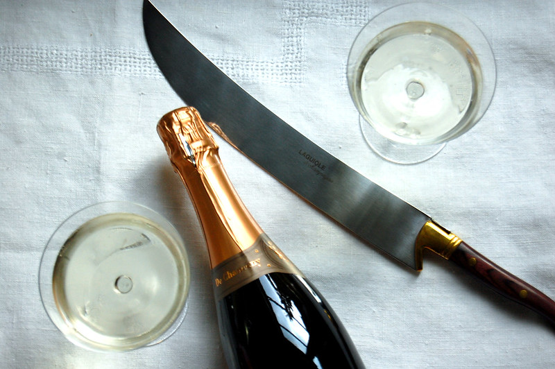 champagne saber with bottle and glasses of champagne