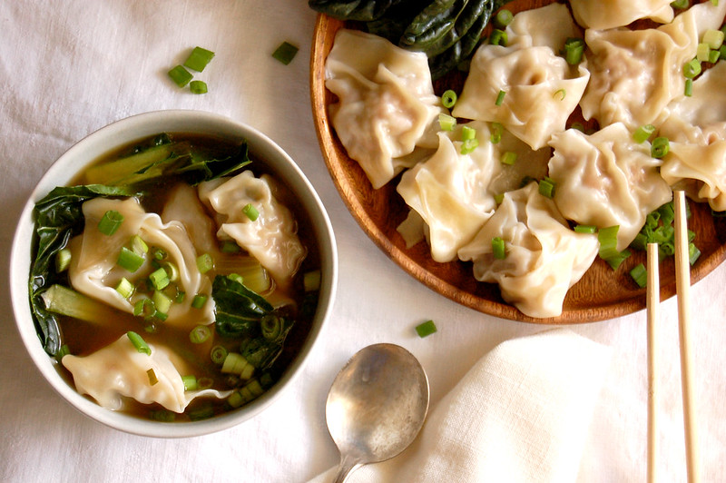 bowl of wonton soup with greens and scallions with dumplings on plate